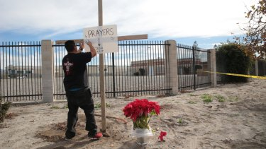 Manny Guzman erects a cross and a sign outside the police perimeter around the Inland Regional Centre, the site of a mass shooting on Wednesday that left 14 dead and 21 wounded, in San Bernardino, California.