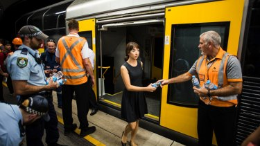 A woman is given water after being trapped on a train near Wynyard Station.