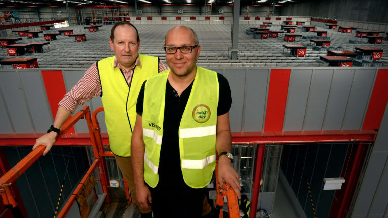 Catch Group head of logistics Jon Northorpe (left) and founder Gabby Leibovich on a cherry picker overseeing the company's $20 million investment in warehouse robots.