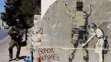 An Israeli soldier walks past a Banksy mural in Bethlehem.