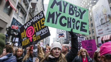 Demonstrators hold signs while marching towards Trump Tower during the Women's March in New York.