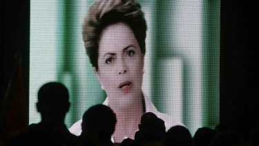 People watch a speech by Brazilian President Dilma Rousseff broadcast on the Workers Party's television program on Thursday evening.