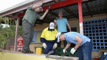 Prime Minister Tony Abbott and Social Services Minister Scott Morrison assist in the community hall upgrade in the Injinoo community.