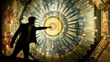 Dr Alan Duffy points to an image of the Compact Muon Solenoid, or CMS, detector at the Collider exhibition at the Powerhouse Museum. The real CMS detector is 15 metres high.
