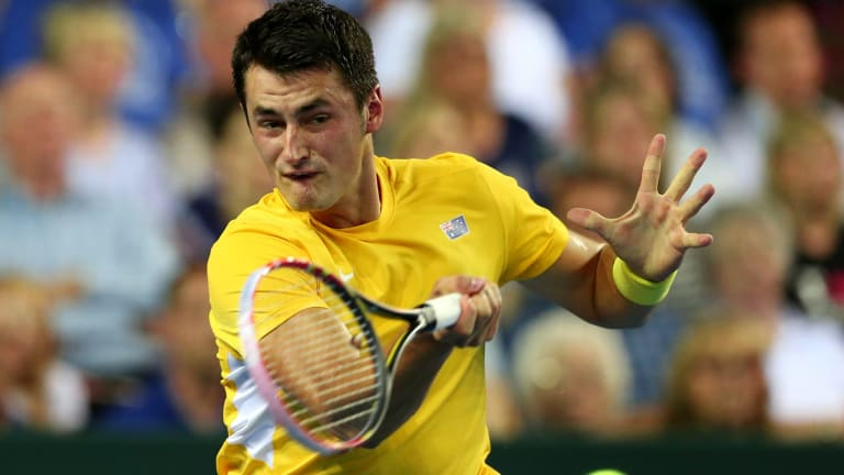 Under pressure: Bernard Tomic plays a forehand return to Britain's Andy Murray.