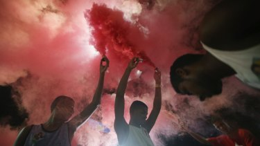 Anti-impeachment protesters light red smoke, the colour of the Workers' Party, in Rio de Janeiro.