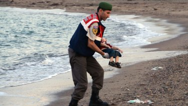 A paramilitary police officer carries the body of Aylan Kurdi after refugees died when boats capsized near the Turkish resort of Bodrum in September.