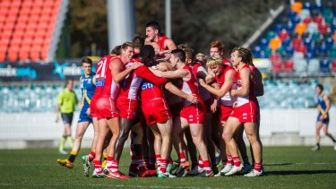 Canberra Demons vs Sydney Swans July 1. Alex Johnson being swarmed by his team mates in celebration after scoring a goal. Photo: Dion Georgopoulos