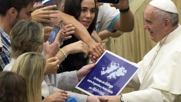"A placard which reads, ""It's time for dialogue between Argentina and the United Kingdom for Falklands"", is held by faithful as Pope Francis is greeted during the weekly audience at the Vatican on Wednesday."
