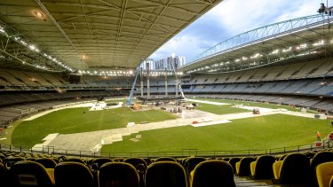 Workers at Melbourne's Etihad Stadium break down the stage after Adele's Sunday night concert. The ground will host a round-one AFL match on Saturday night.