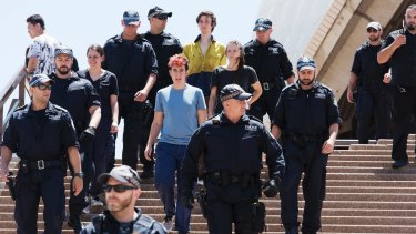 The arrested activists are escorted to police vehicles after being brought down from the Sydney Opera House sails.