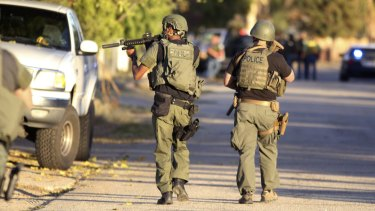 Police at the scene of a shootout about a mile from the site where gunmen left at least 14 dead.