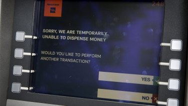 A message is displayed on the monitor of a Piraeus Bank ATM in Athens.