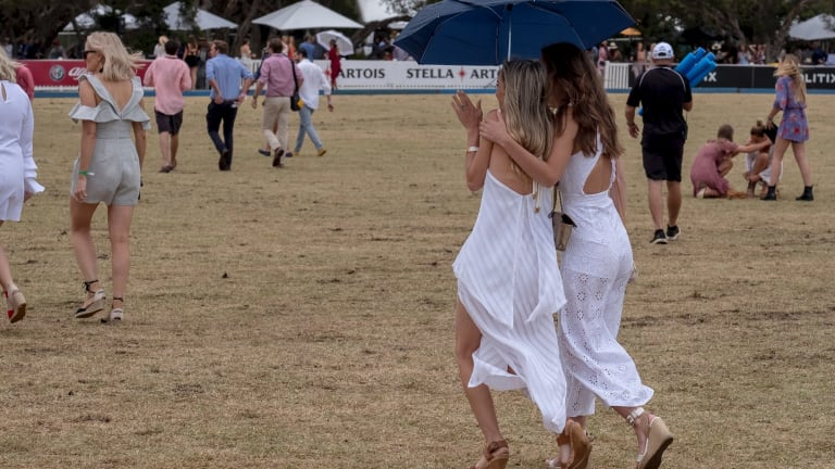 Women shelter under umbrellas at the Portsea Polo on Saturday.