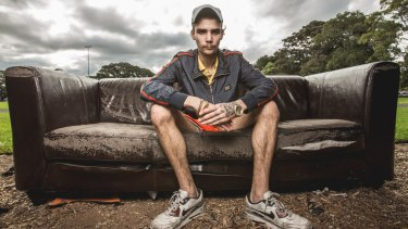 Jaike Digney has few photo opportunities and posed for his portrait on a discarded couch.