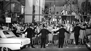Police officers hold back the tide of fans screaming for the Beatles outside the Sheraton Hotel, where they stayed in Sydney during their 1964 Australian tour.