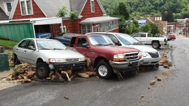 Cars and large rocks are smashed together after being carried down Oakford Avenue by flood waters in Richwood, West Virginia.