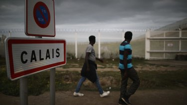 Migrants walk past secuirty fencing at the 'Jungle' migrant camp in Calais.