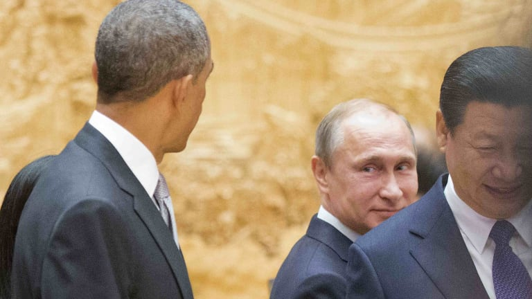 Russian President Vladimir Putin, centre, looks back at US President Barack Obama, left, as they arrive with Chinese President Xi Jinping at the APEC summit.