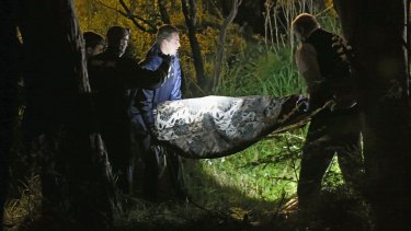 Police remove the body of a woman from bushland in Donvale.