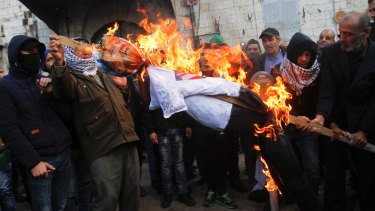 Palestinian protesters burn an effigy of US President Donald Trump during a protest against the decision to recognise Jerusalem as Israel's capital.