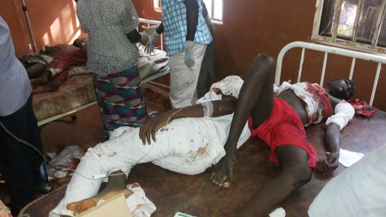 People are treated at the General hospital in Potiskum after a suicide bomb attack at a school assembly.