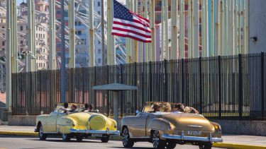 Tourists ride vintage American convertibles as they pass by the United States embassy in Havana, Cuba.
