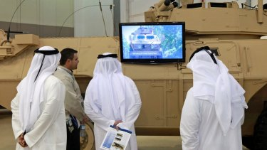 Visitors at the 2011 IDEX arms fair in Abu Dhabi, the United Arab Emirates, watch a promotional video for the M1117 armoured vehicle, manufactured by Textron Systems.