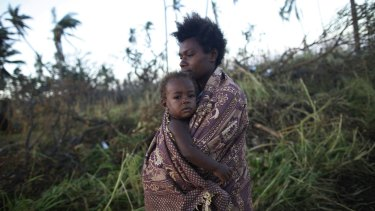 A woman carrying her baby walks past fallen trees in Tanna.