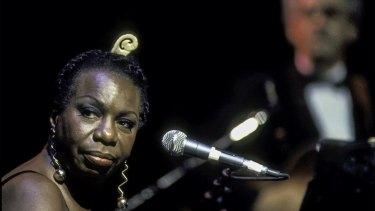 American musician and Civil Rights activist Nina Simone (born Eunice Kathleen Waymon, 1933 - 2003) performs at the Beacon Theater, New York, New York, May 1, 1993. Guitarist Al Shackman is visible, though out of focus, in the background. (Photo by Jack Vartoogian/Getty Images)