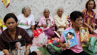 Well-wishers hold portraits of the king as they wait for him to leave hospital in  2013.