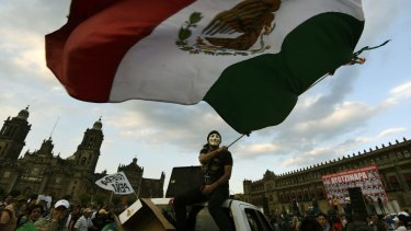 People take part in a march commemorating four months of the disappearance of 43 students from Ayotzinapa, at the Zocalo square in Mexico City.