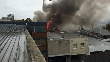 Flames break through the roof of a building on Alexander Street in Crows Nest.