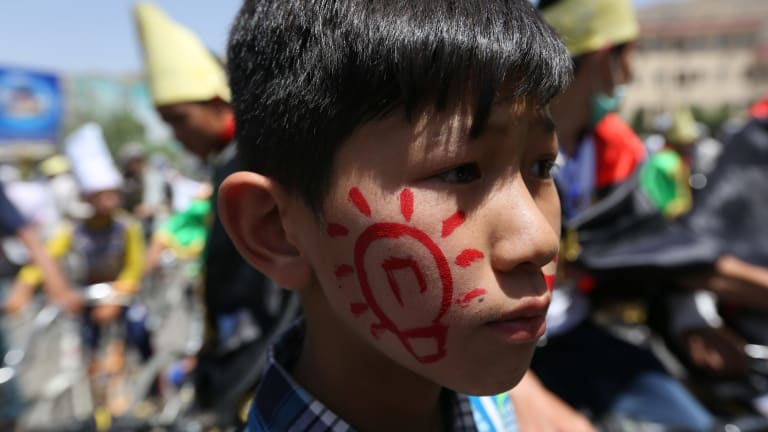 A young Hazara wears a symbol of electricity as thousands of demonstrators march towards the centre of Kabul, Afghanistan.