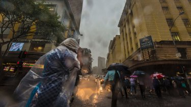 Workers leave the Brisbane CBD as ex-cyclone Debbie hits south-east Queensland.