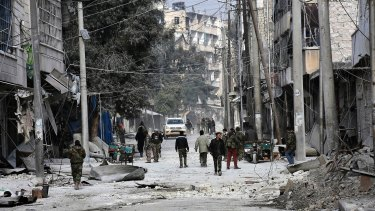 Syrian soldiers and civilians marching through the bomb-damaged streets of east Aleppo.