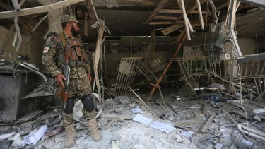 An Afghan security guard stands inside the bank after the explosion.