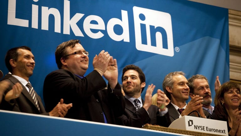 Reid Hoffman, chairman and co-founder of LinkedIn, left, and chief executive Jeff Weiner, centre, applaud during the opening bell ceremony at the New York Stock Exchange as LinkedIn listed in 2011.  Microsoft announced this week that it's buying LinkedIn for a whopping $US26.2 billion ($35.5 billion).
