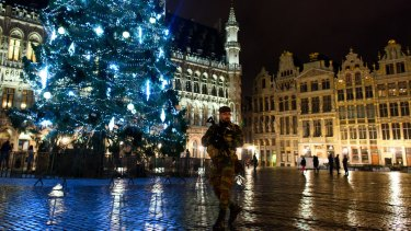 An armed soldier stands guard over the Grote Markt in Brussels on Monday. Security has been tightened in the nation's capital after police arrested 16 suspected terrorists during more than 22 anti-terror raids around the city on Sunday.