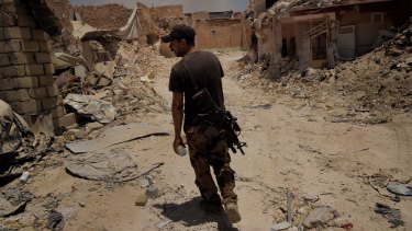 An Iraqi Special Forces soldier walks through the streets of West Mosul, Iraq, last week.