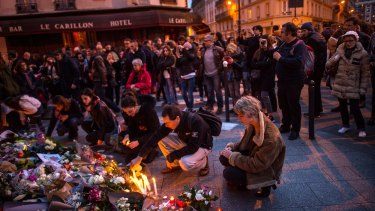 Mourners leave candles in front of the Petit Cambodge restaurant with the Le Carillon restaurant in the background.