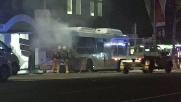 Firefighters extinguish a fire on a bus in George Street, Sydney, on Thursday night.