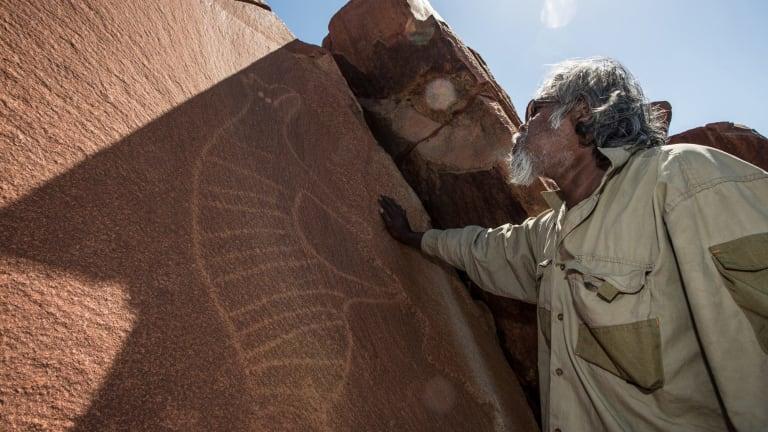 Senior cultural ranger at Murujuga National Park, Jakari Togo, stands next to a rock carving of a thylacine on the Burrup Peninsula, Western Australia.