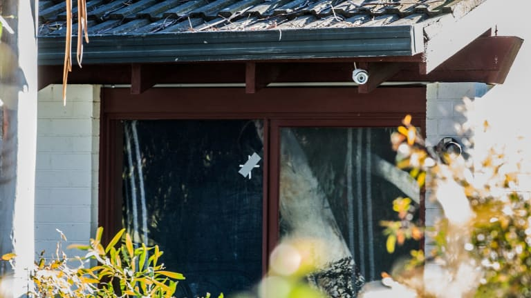 Bullet holes in the window of the Waramanga home targeted in Tuesday night's shooting.