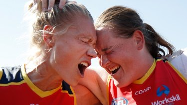 Adelaide's Erin Phillips (left) and Sarah Perkins belt out  the team song after their win against Collingwood on Sunday.