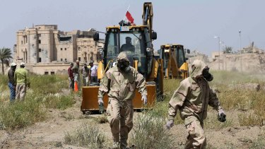 An Iraqi forensic team in the city of Tikrit works at the site of a mass grave, believed to contain the bodies of Iraqi soldiers massacred by the so-called Islamic State in June.
