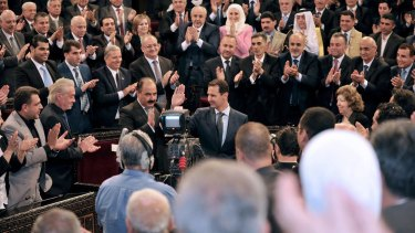 Syrian President Bashar al-Assad waves before addressing the newly-elected parliament in Damascus, Syria.