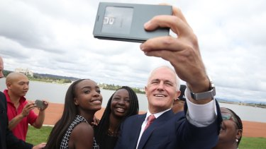 Prime Minister Malcolm Turnbull takes a selfie with new Australian citizens Lydia Banda-Mukuka and Chilandu Kalobi Chilaika after the citizenship ceremony on Australia Day in Canberra.
