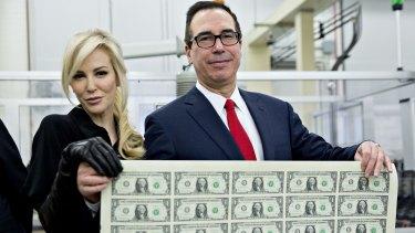 US Treasury Secretary Steven Mnuchin and his wife Louise Linton hold a sheet of $1 notes bearing Mnuchin's name.