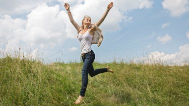 Young woman running through field with arms in air